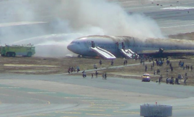 The 777 burns on the runway at SFO. (NTSB)