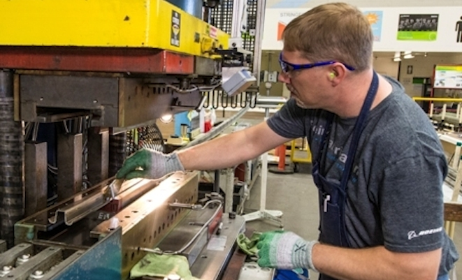 Joggle Press operator Rich Harrison prepares the first 737 MAX fuselage stringer for the press by brushing on lubricant. (Boeing)