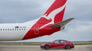 A Qantas Boeing 737-800 VH-XZI and a Tesla Model S electric car at Avalon Airport. (Qantas)