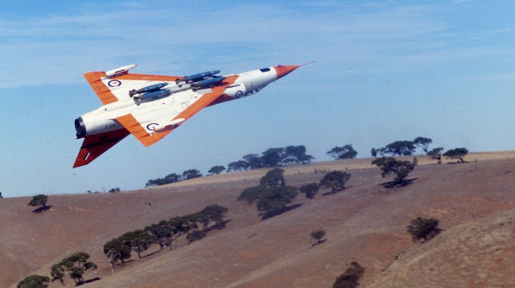 A3-2 Mirage III of ARDU, 3/4R view of A/C inverted over a hill near Woomera, A/C fitted with pylon & 6 MK82 500lb bombs. A/C file 3-3-392