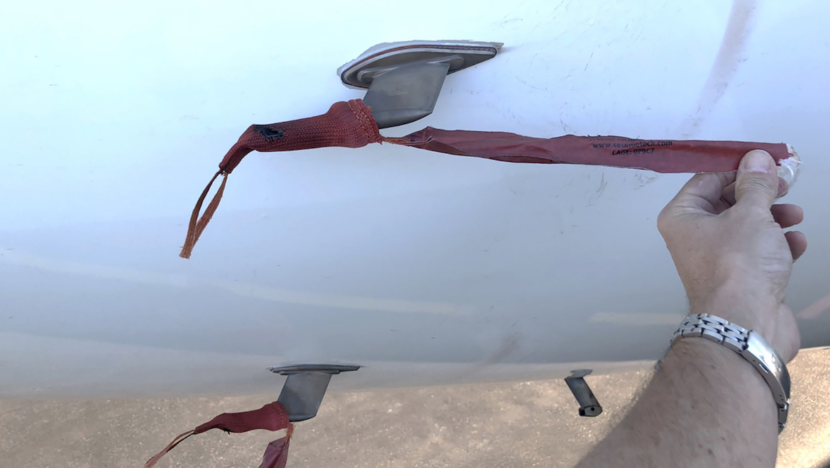 Pitot probe covers on Malaysia Airlines Airbus A330-300 9M-MTK, showing pitot cover damage and rub marks on aircraft skin from the streamer. (ATSB)