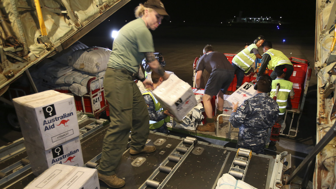 A Royal Australian Air Force C-130J Hercules aircraft is unloaded of humanitarian aid cargo by hand in Balikpapan, Indonesia. (Defence)