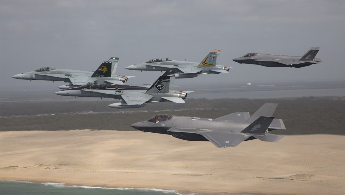 Royal Australian Air Force F/A-18 Hornets fly in formation with a pair of F-35A Joint Strike Fighters over Stockton Beach, NSW. (Defence)