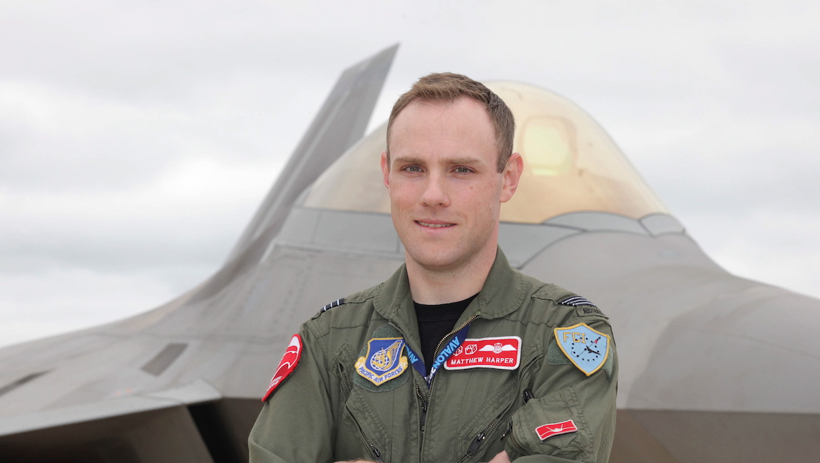 RAAF Squadron Leader Matt Harper at the 2011 Avalon Airshow with the F-22 Raptor in the background. (Defence)