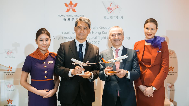 Flight attendants flank Hong Kong Airlines vice chairman Tang King-shing and Virgin Australia chief executive John Borghetti. (Virgin Australia)
